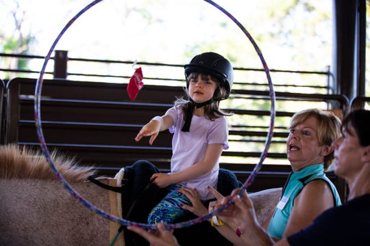Kimmy McGrail, 5, is coached by her occupational therapist, Mary Fellenz, to through a pouch through the hula-hoop. The exercise is a way to help improve Kimmy's hand-eye coordination during her Hippotherapy session on Wednesday morning, on Sept. 20, 2018, at Naples Therapeutic Riding Center.