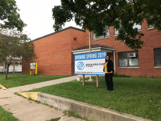 Amanda Vozzella, founding director of the Boys & Girls Club of Newark, stands next to the sign announcing the club's opening in 2019.