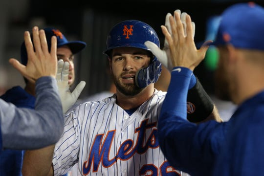 New York Mets catcher Kevin Plawecki (26) celebrates in the dugout with teammates after hitting a solo home run against the Atlanta Braves during the third inning at Citi Field.