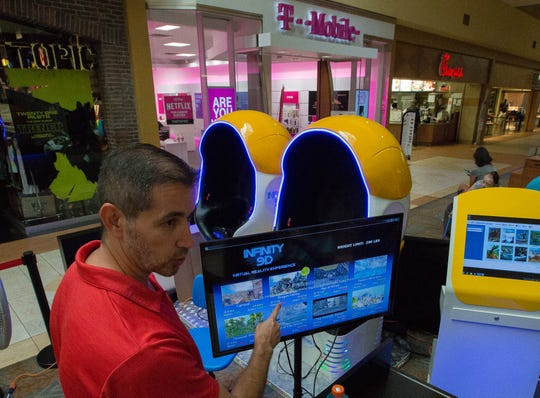 Rick Morales, owner and operator of the Virtual Reality Zone at the Mesilla Valley Mall, explains the different games he offers to customers.