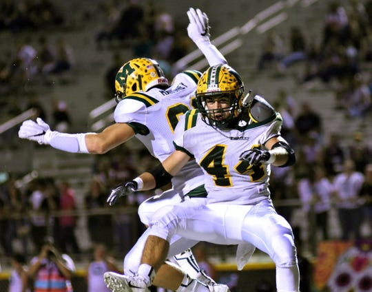 Mayfield's AJ Parra (44) celebrates with teammate Brandon Mahoney after he intercepted a pass and ran it back for a touchdown Thursday night at the Field of Dreams.