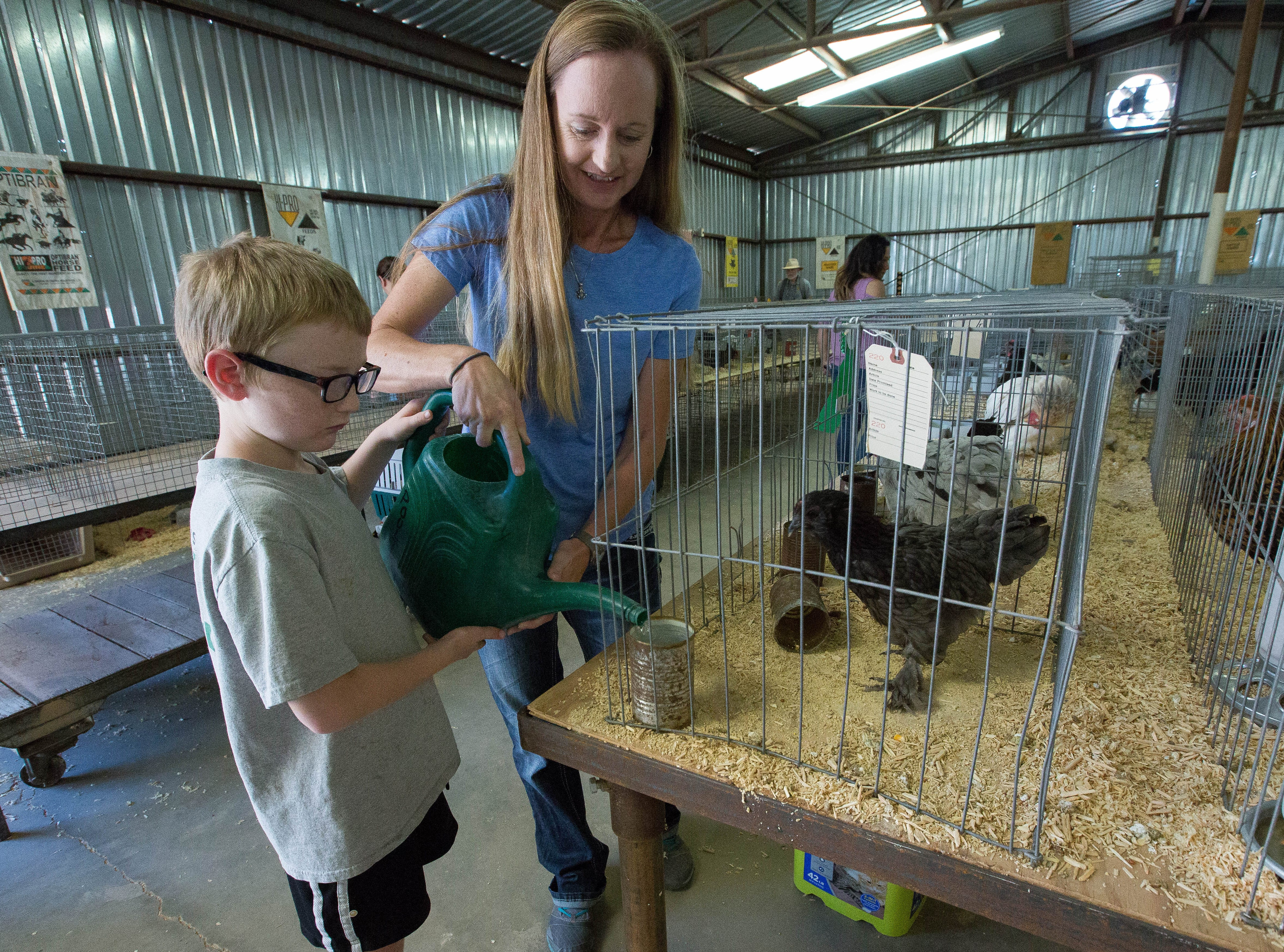 Brody Kirby, 7, and his mom Melissa Kirby, water Larson Kirby's chickens in the Poultry barn at the Southern New Mexico State Fair and Rodeo, Friday September 28, 2018.