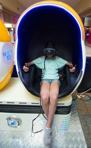 Alex Morales, 11,  demonstrates how the virtual reality headsets work at her father's Virtual Reality Zone at the Mesilla Valley Mall Friday September 28, 2018.