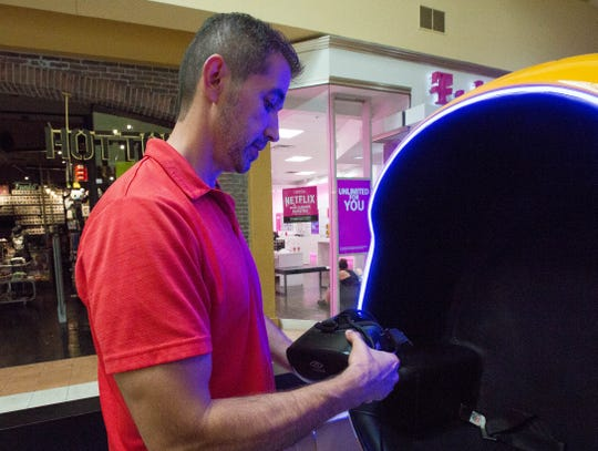 Rick Morales, owner and operator of the Virtual Reality Zone at the Mesilla Valley Mall, explains how the VR goggles work when you play one of the games he offers to customers.