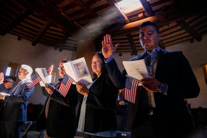 Juan Luis Núñez, left, Norman Enriquez, Rudolpho Mosqueda, Nenita Mosqueda and Jose Luis Perez take the oath of U.S. citizenship Friday during a naturalization ceremony at Aztec Ruins National Monument.