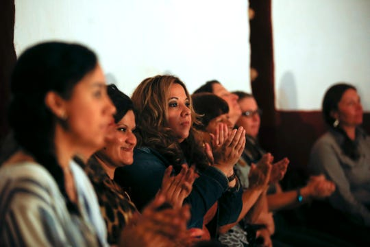 Audience members applaud after eight individuals took their oath of citizenship Friday during a naturalization ceremony at Aztec Ruins National Monument.