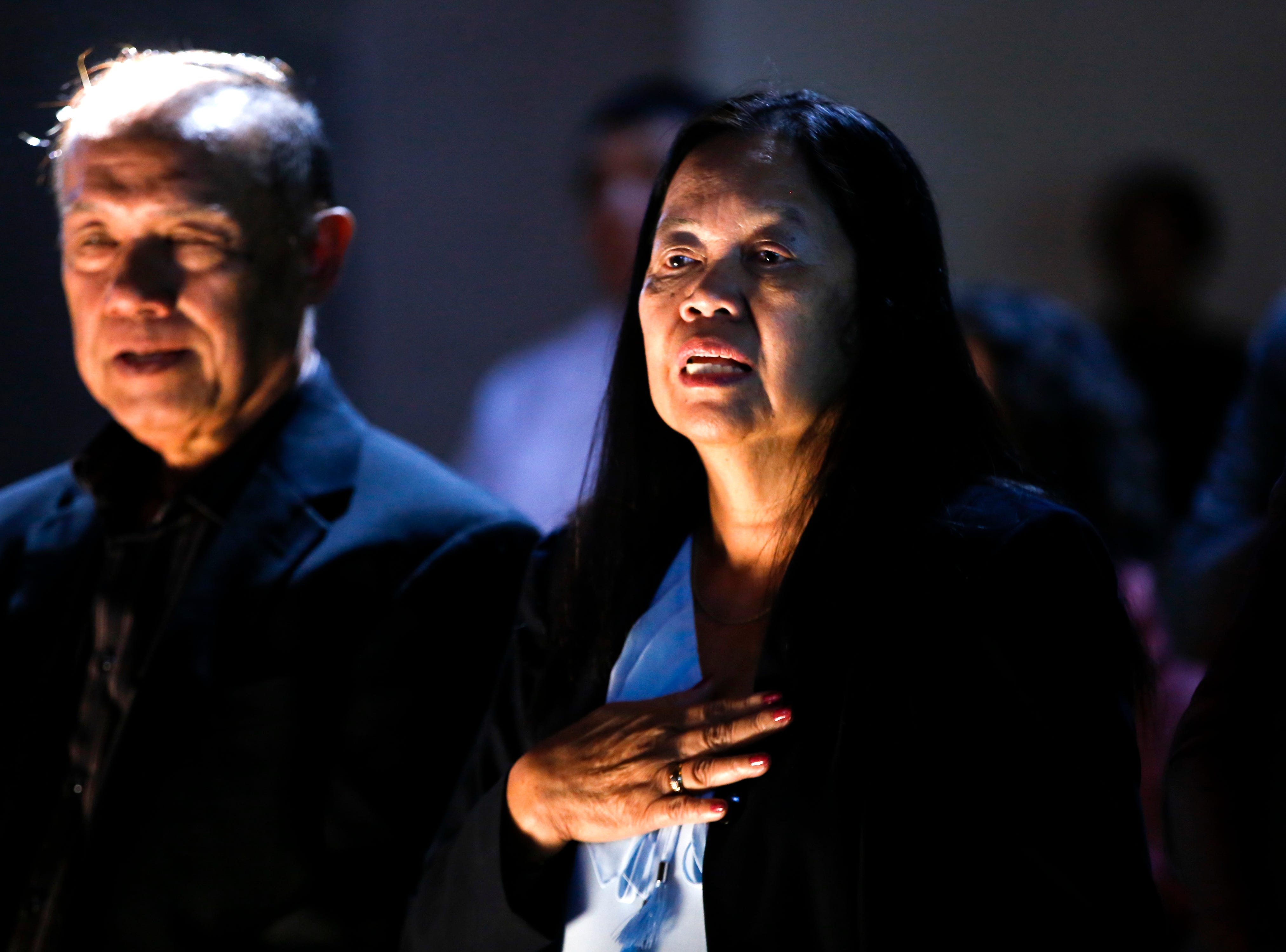 Rudolpho Mosqueda, left, and his wife Nenita Mosqueda sing the United States National Anthem, Friday, Sept. 28, 2018 before taking part in a naturalization ceremony at the Aztec Ruins National Monument.