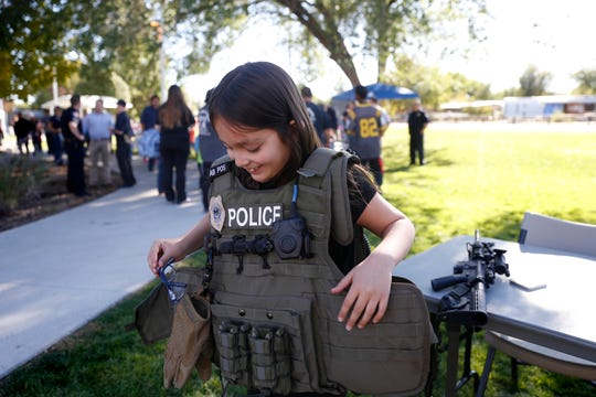 Blythe Kreitinger tries on a Farmington Police Department tactical vest during the Farmington Police Department's National Night Out event last year at the Boys & Girls Clubs in Farmington.