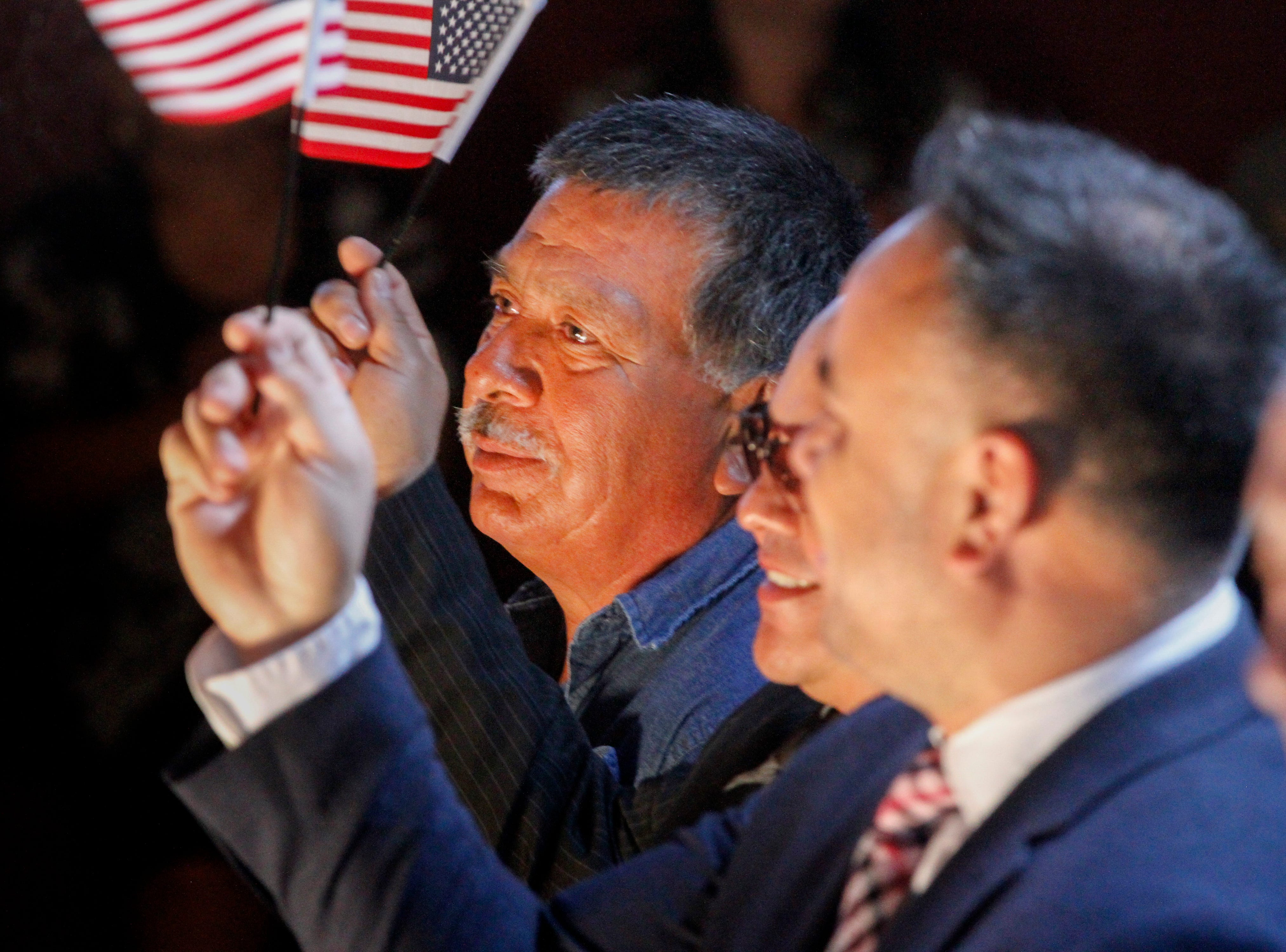 Jose Javier Juarez, left, Juan Luis Núñez and Norman Enriquez wave the U.S. Flags after taking the oath of citizenship, Friday, Sept. 28, 2018 during a naturalization ceremony at the Aztec Ruins National Monument.