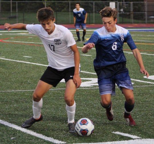 North Farmington's Ryan Haas (17) and Farmington's Matthew Demartini (6) battle for ball control in the first half of Thursday's intense intra-city boys soccer game.
