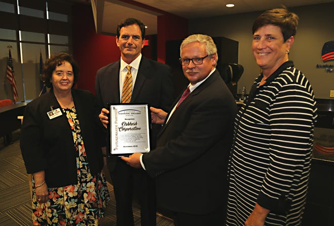 Oshkosh Corporation CEO Wilson Jones receives the WTCS Futuremaker Partner award from WTCS Board President Mark Tyler. Fox Valley Technical College President Dr. Susan May (L) and System President Dr. Morna K. Foy (R) joined in the presentation.