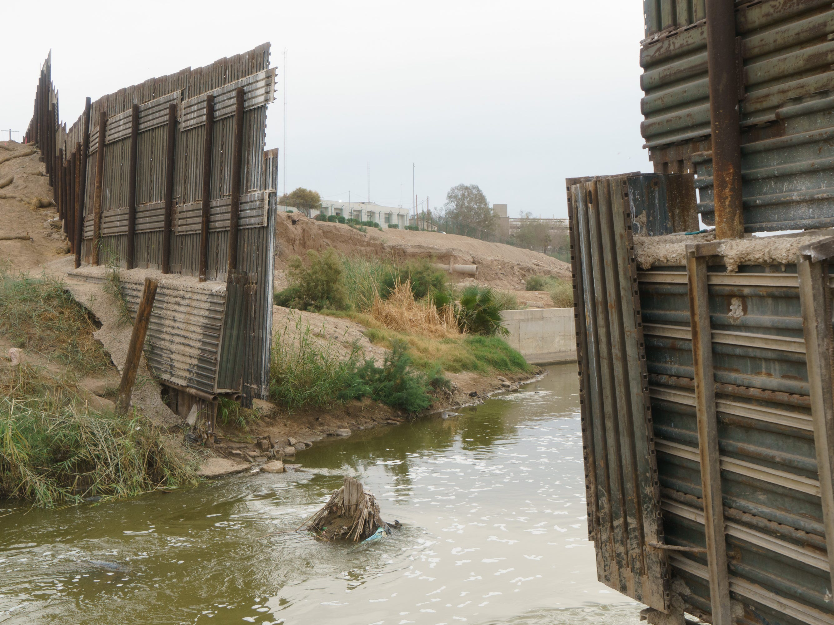 The New River flows across the border into California. This section of the border fence was recently removed and replaced with a new, taller barrier.