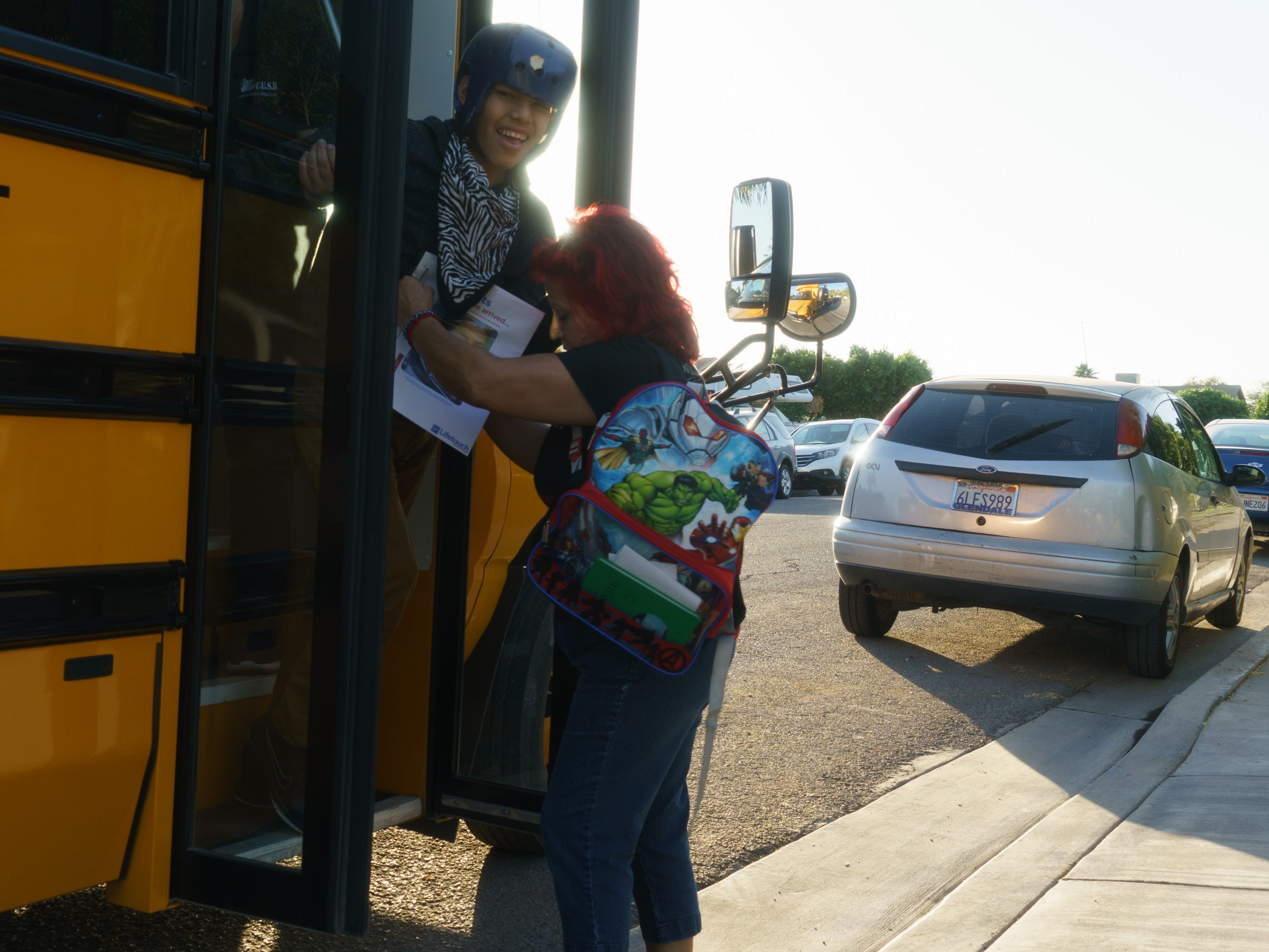 Candelaria Nieblas helps her son Jesús Iván off the school bus in Calexico. They live in the neighborhood next to the New River.