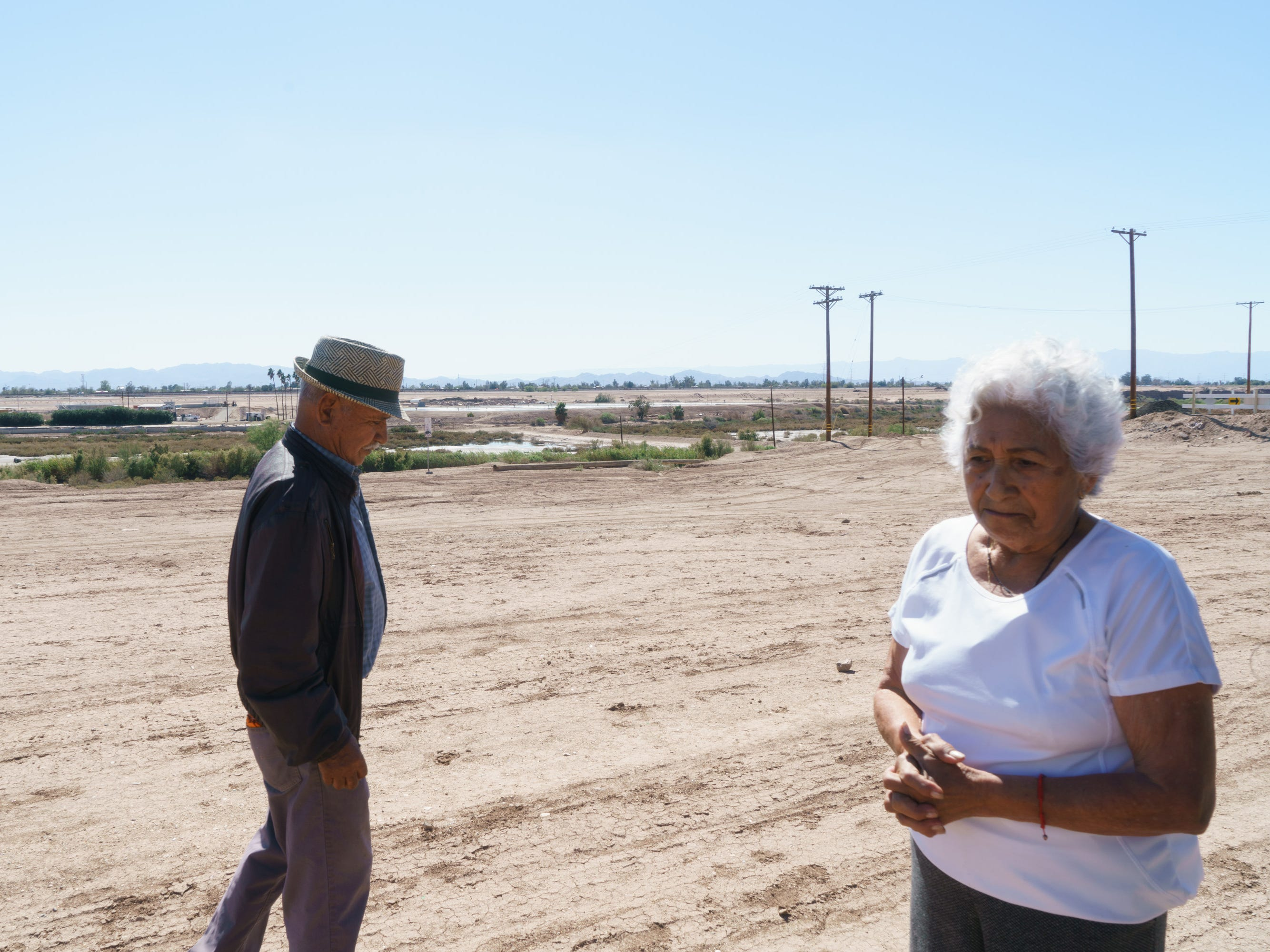 Miguel and Rebeca Zapata walk on a bare patch of dirt between their backyard and the banks of the New River.