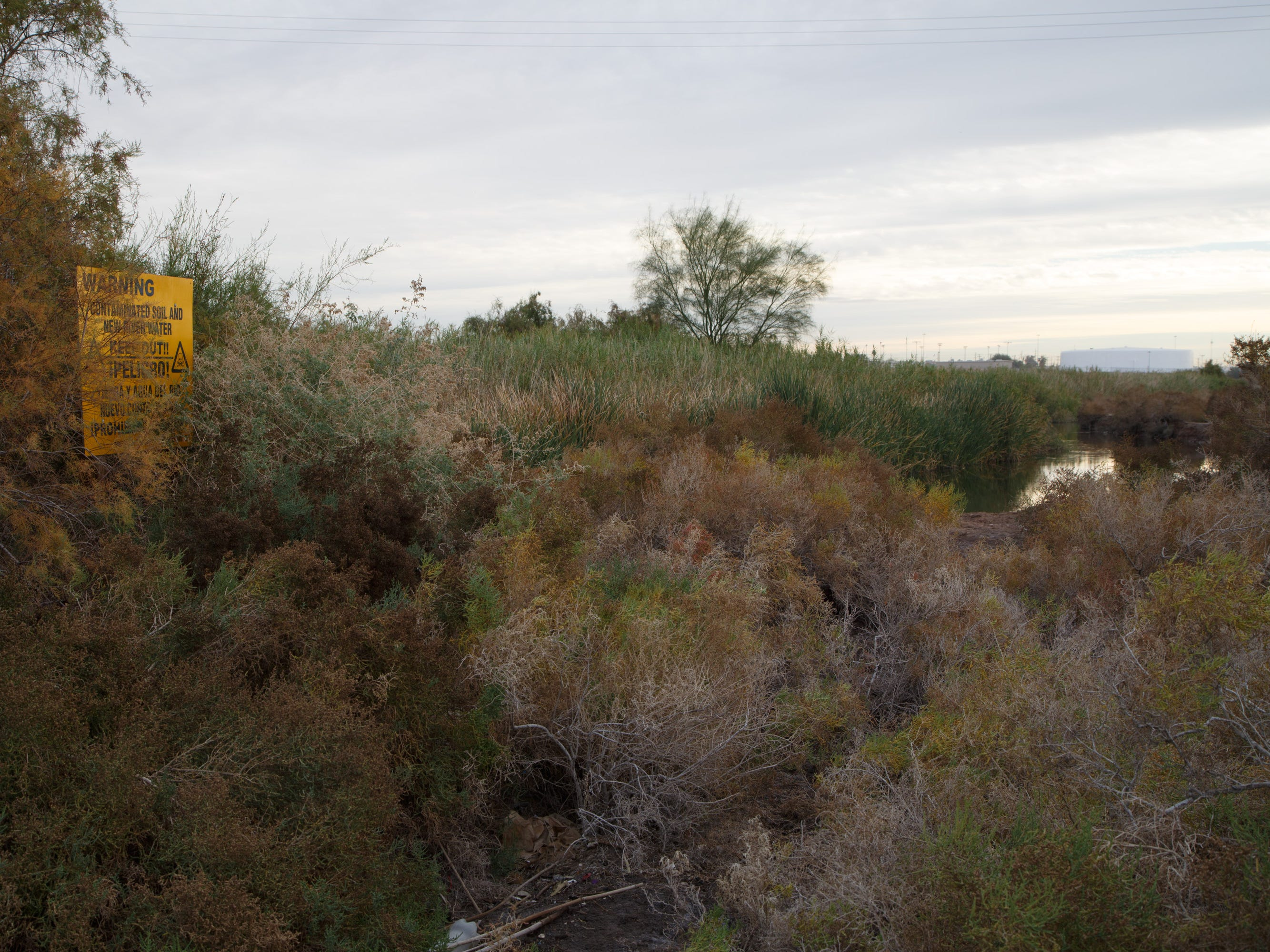 A sign beside the New River warns that the soil and water are contaminated and that people should keep out.