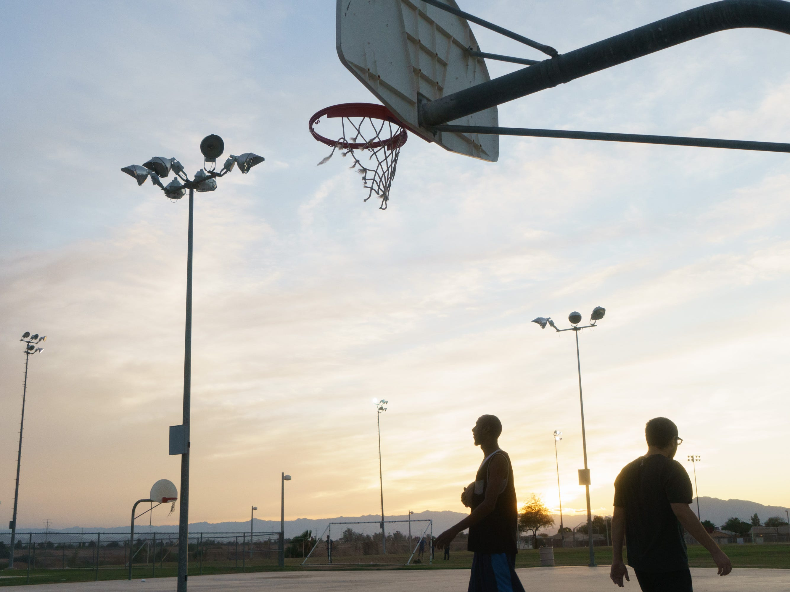 André Walker, left, and Noor Hijazi play basketball in Calexico. The courts are next to a Little League field and close to the banks of the New River.