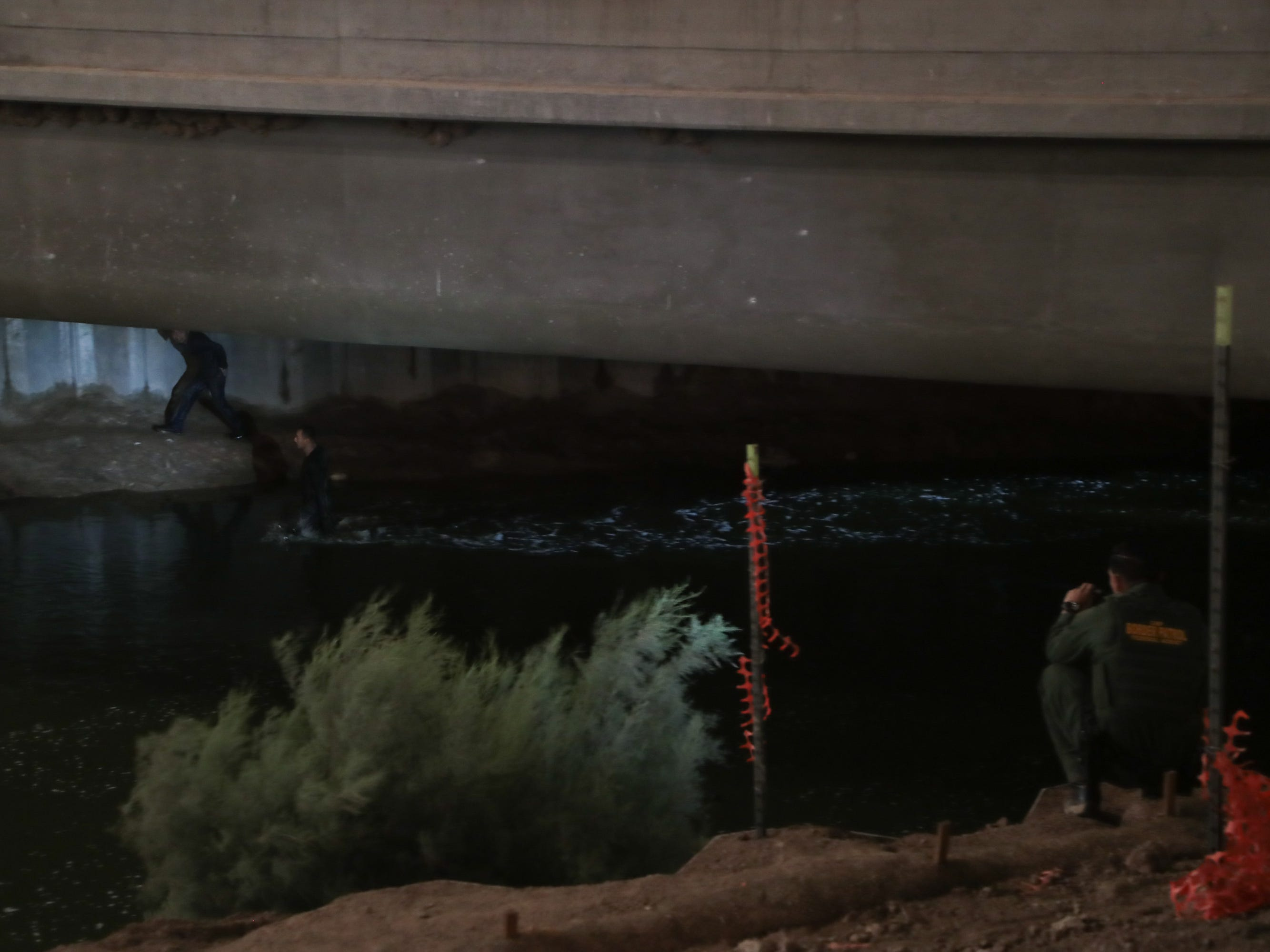 Border Patrol Agent Ruben Sigala shines his flashlight on migrants attempting to cross into the United States through the New River in Calexico on Sept. 19, 2018.