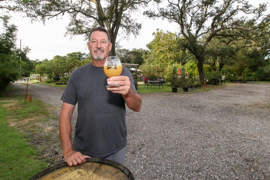 Gary Yetter, owner of Gary's Home Brew Supply and Artisan Crafted Beers, holds a glass of beer in the backyard area of the property on Thursday.