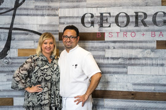 """George Bistro + Bar owner George Lazi and his wife Luba stand against what Luba calls the """"Instagram wall"""" on Friday, Sept. 28, 2018."""