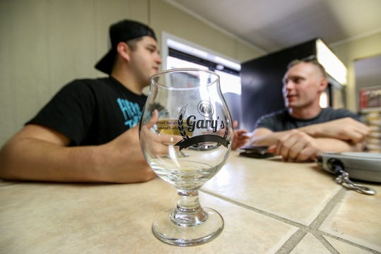 John Jimenez, left, chats over a beer with Jesse Jolley on Thursday at Gary's Home Brew Supply and Artisan Crafted Beers.