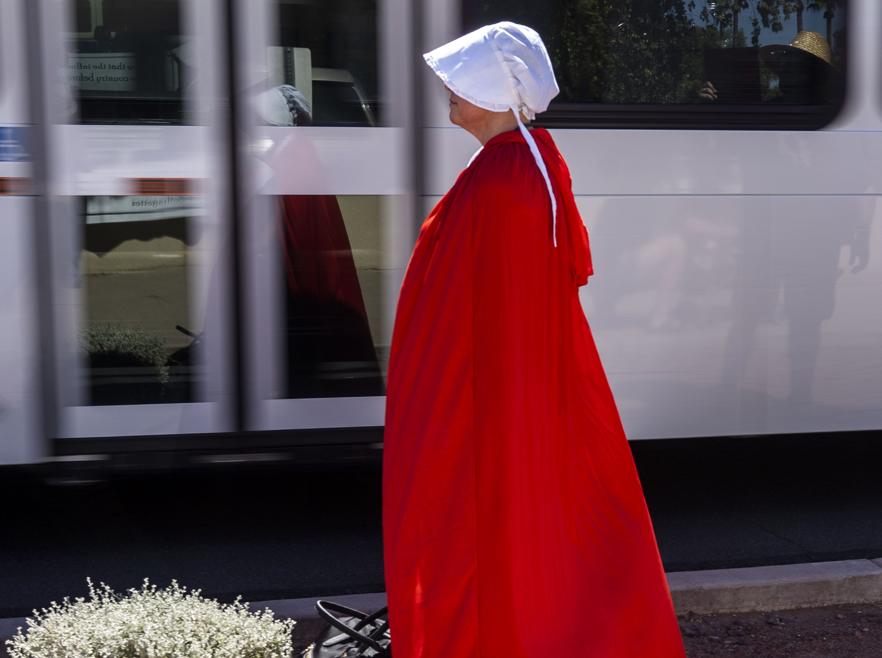 """A protester dressed as a handmaid from """"A Handmaid's Tale"""" marches Sept. 28, 2018, outside Jeff Flake's office in Phoenix. Flake said he wouldn't support a floor vote for Judge Brett Kavanaugh U.S. Supreme Court confirmation without allowing an investigation into sexual harassment accusations against Kavanaugh."""