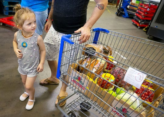 Raelyn Dawley, 2, receives food with her father Brandon at United Food Bank in Mesa, Arizona, on Sept. 28, 2018.