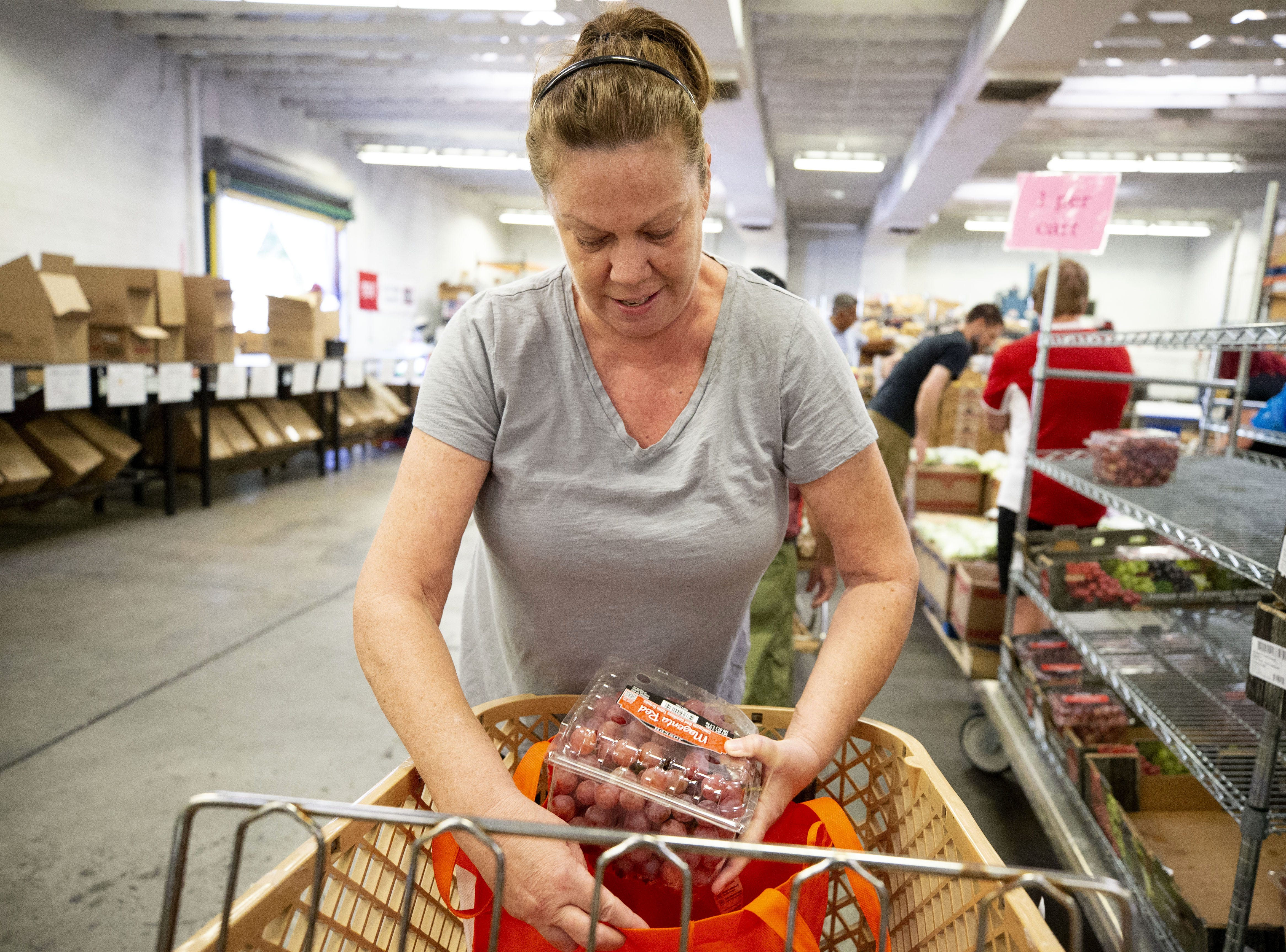 Mary Buchanan, of Mesa, receive food from United Food Bank in Mesa on September 28, 2018.