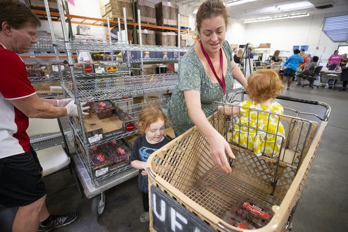 United Food Bank volunteer Clint Watson helps Shawna Dorner, and her children Theodore, 3, and Claire, 2, of Apache Junction, with food distribution in Mesa on September 28, 2018.