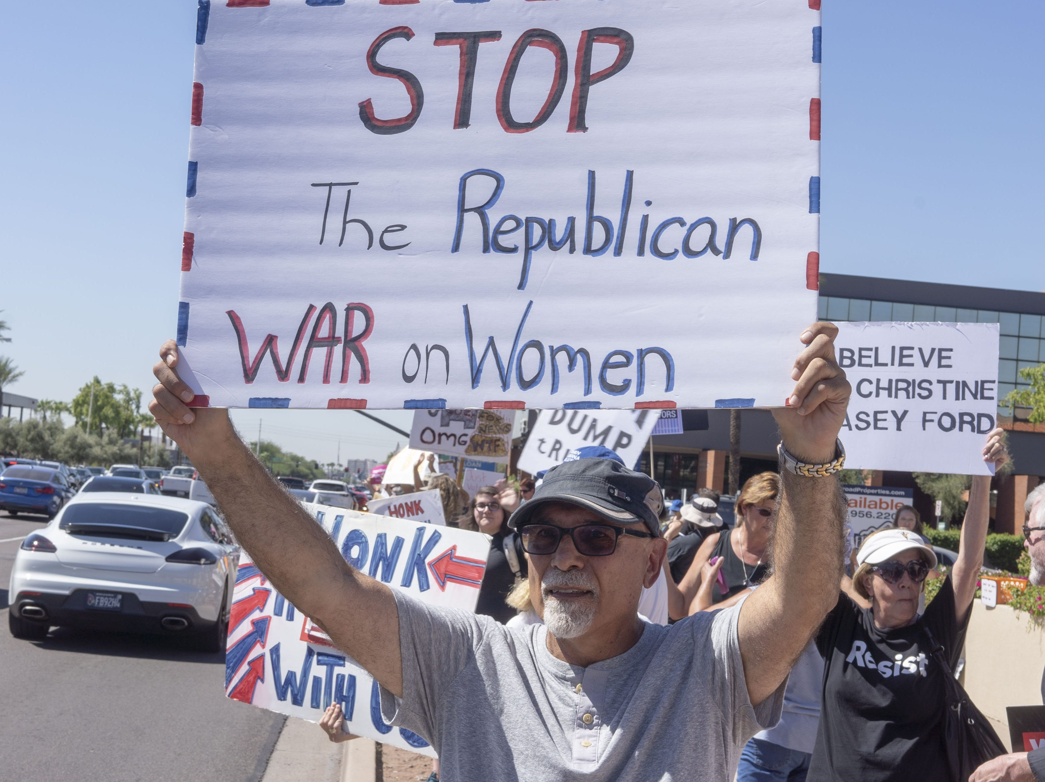 Norman Weinglass holds a sign during a protest Sept. 28, 2018, outside of Jeff Flake's office in Phoenix. Flake said he wouldn't support a U.S. Senate floor vote for Judge Brett Kavanaugh's Supreme Court confirmation without first allowing an FBI investigation into sexual harassment accusations against Kavanaugh.