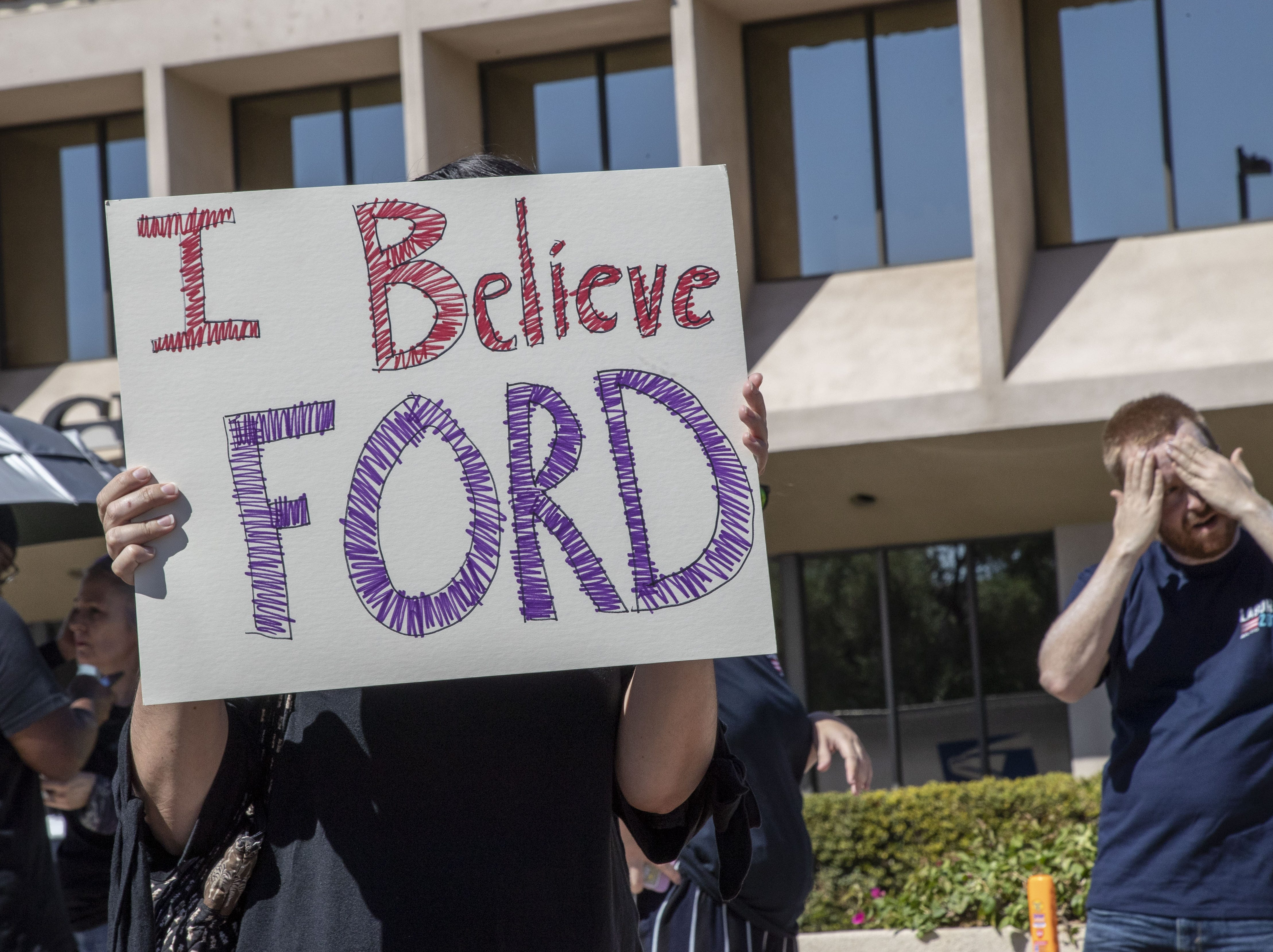 People protest Sept. 28, 2018, outside Jeff Flake's Phoenix office after he said wouldn't support a U.S. Senate floor vote for Judge Brett Kavanaugh's Supreme Court confirmation without first allowing an FBI investigation into sexual harassment accusations against Kavanaugh.