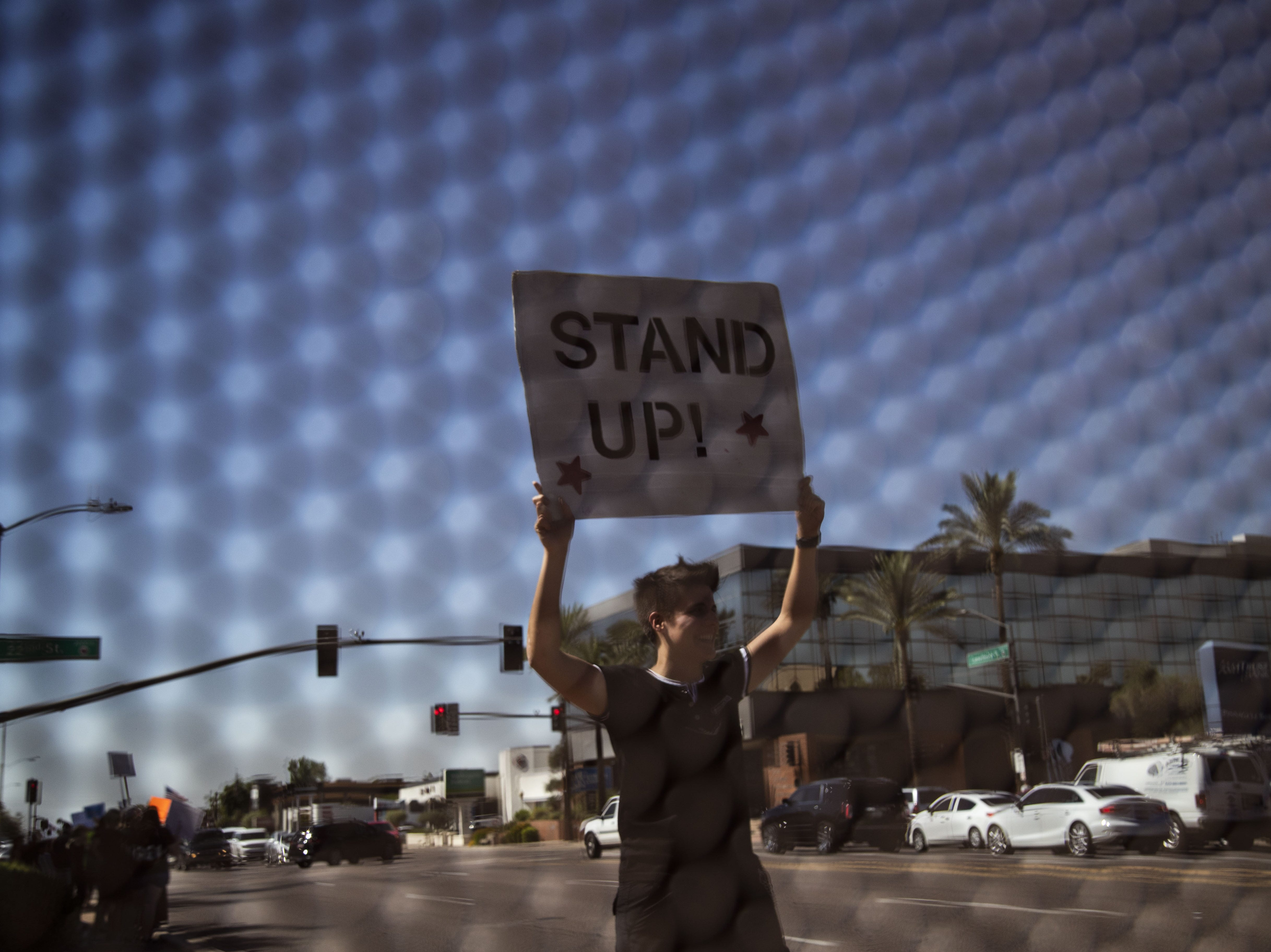Phoenix resident Jessica Spencer protests Sept. 28, 2018, outside of Jeff Flake's office in Phoenix after he said he wouldn't support a U.S. Senate floor vote for Judge Brett Kavanaugh's Supreme Court confirmation without first allowing an FBI investigation into sexual harassment accusations against Kavanaugh.