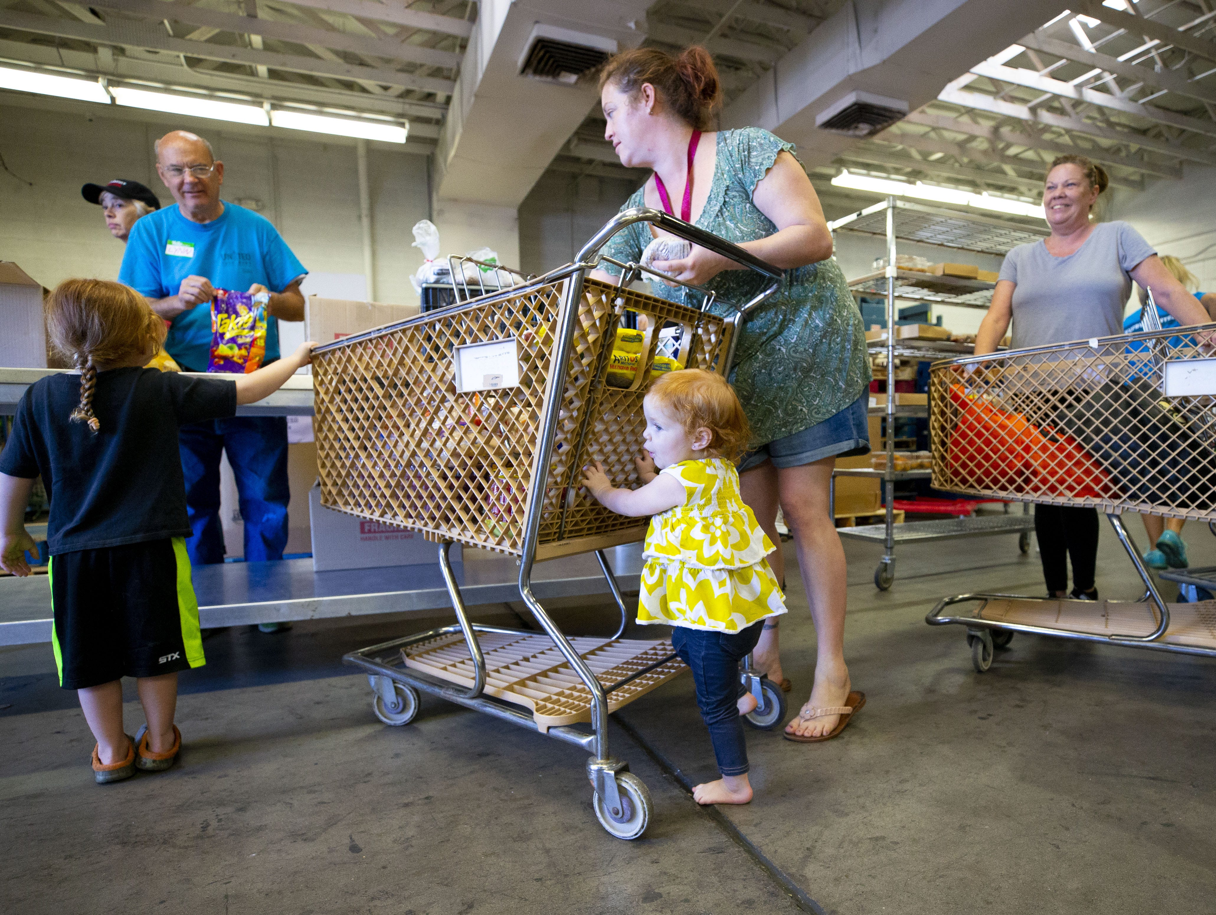 Shawna Dorner, and her children Theodore, 3, and Claire, 2, of Apache Junction, receive food from United Food Bank in Mesa on September 28, 2018.