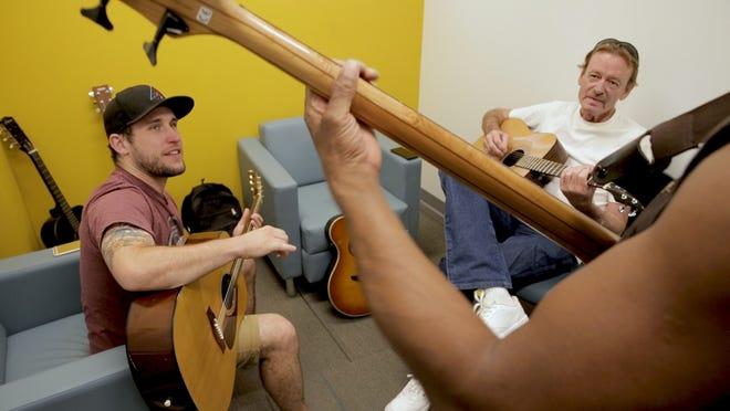 Nathaniel Shrake (left), a former Marine, teaches guitar as part of the Westward Ho Collaboratory.