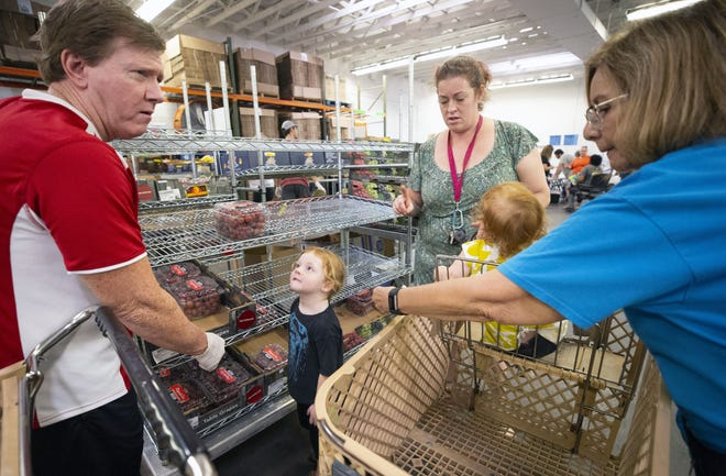 United Food Bank volunteers Clint Watson, left, and Barbara Ontiveros, right, assist Shawna Dorner, and her children Theodore, 3, and Claire, 2, of Apache Junction, with food distribution in Mesa on Sept. 28, 2018.
