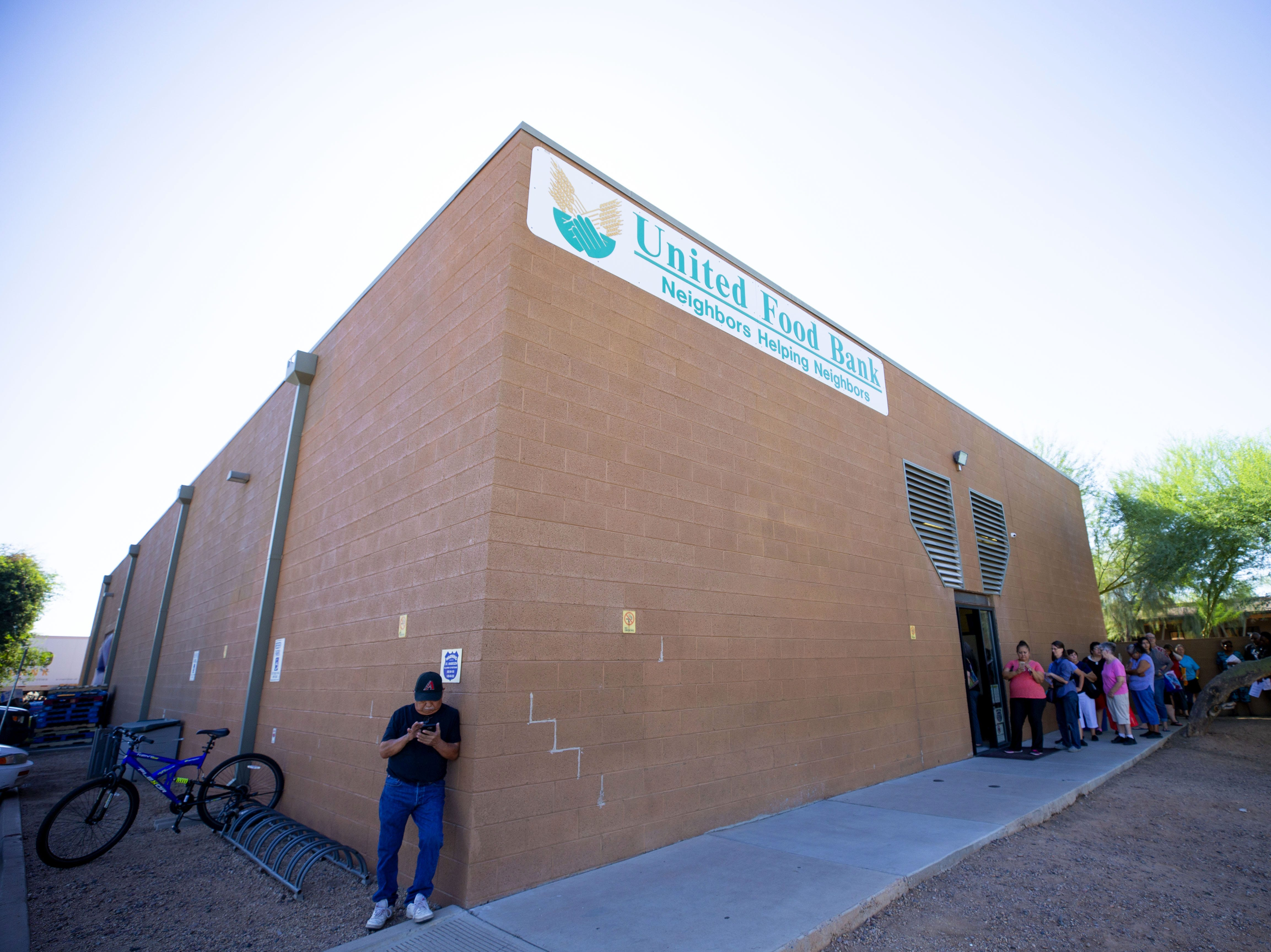 People wait in line at the United Food Bank in Mesa for food distribution on September 28, 2018.