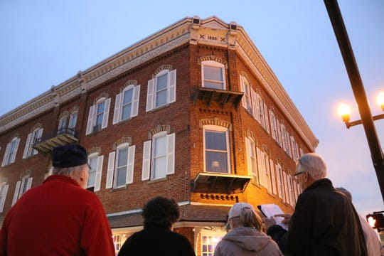 William Gordon, right, described this structure built in 1886, the Island House Hotel, as one of his favorites on the historical walking tour of downtown Port Clinton, which he led during the last Art Walk of the year on Thursday.