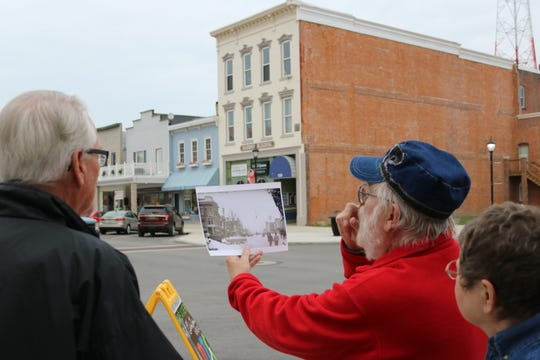 Fred Schwan holds up a decades-old photograph of the same street corner, Madison and Second streets, during a historical walking tour of downtown Port Clinton on Thursday.