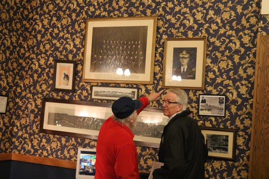 Fred Schwan, left, and William Gordon check out historical photographs displayed in the lobby of the Island House Hotel in downtown Port Clinton.