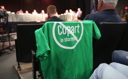 """A T-shirt reading """"Copart in Stormville"""" with a line through it hangs on the back of a chair in the John Jay High School auditorium on Thursday night. The East Fishkill town board meeting allowed time for public comments on the possible sale of the Stormville Airport to the company Copart."""