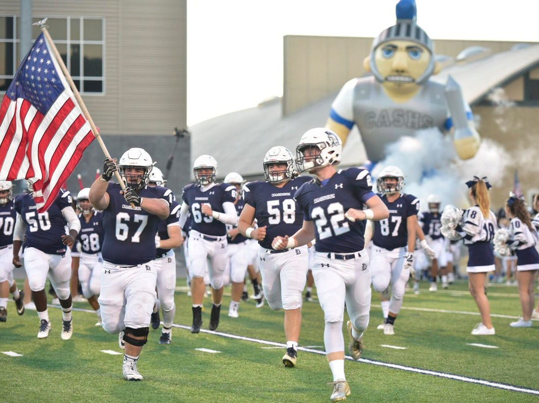 Chambersburg's football team runs onto the field before the game against Cumberland Valley.