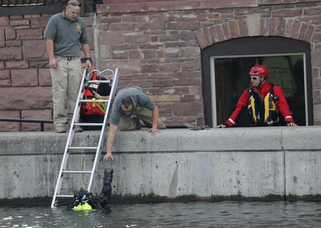 A Monroe County Sheriff's department diver hands something to a team member. The team is searching the Erie Canal in Brockport for evidence in connection with the double homicide in Hamlin.