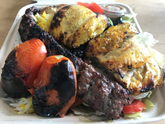 A kubideh and joojeh kebob combo platter at Chortke Kabob, served with rice, salad and grilled plum tomatoes.