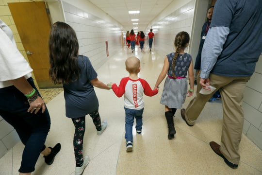 Wyatt Monacelli, 4, who has acute lymphoblastic leukemia, holds hands with sisters Harper, 9, left, and Greta, 7, on their way to a pep rally at Fairport High School.