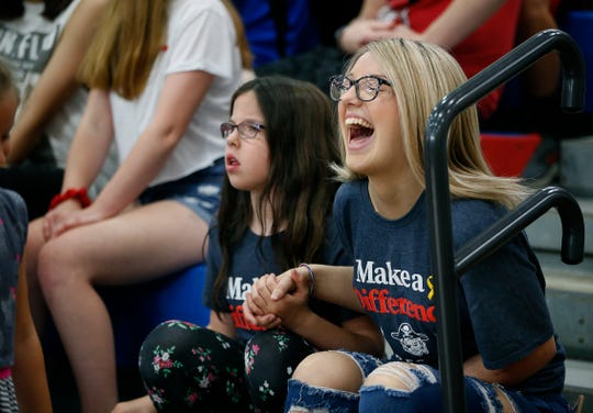 Harper Monicelli, 9, whose brother Wyatt has acute lymphoblastic leukemia, hangs out with Taylor Wilson, 16, who has Ewing sarcoma, during a pep rally at Fairport High School.
