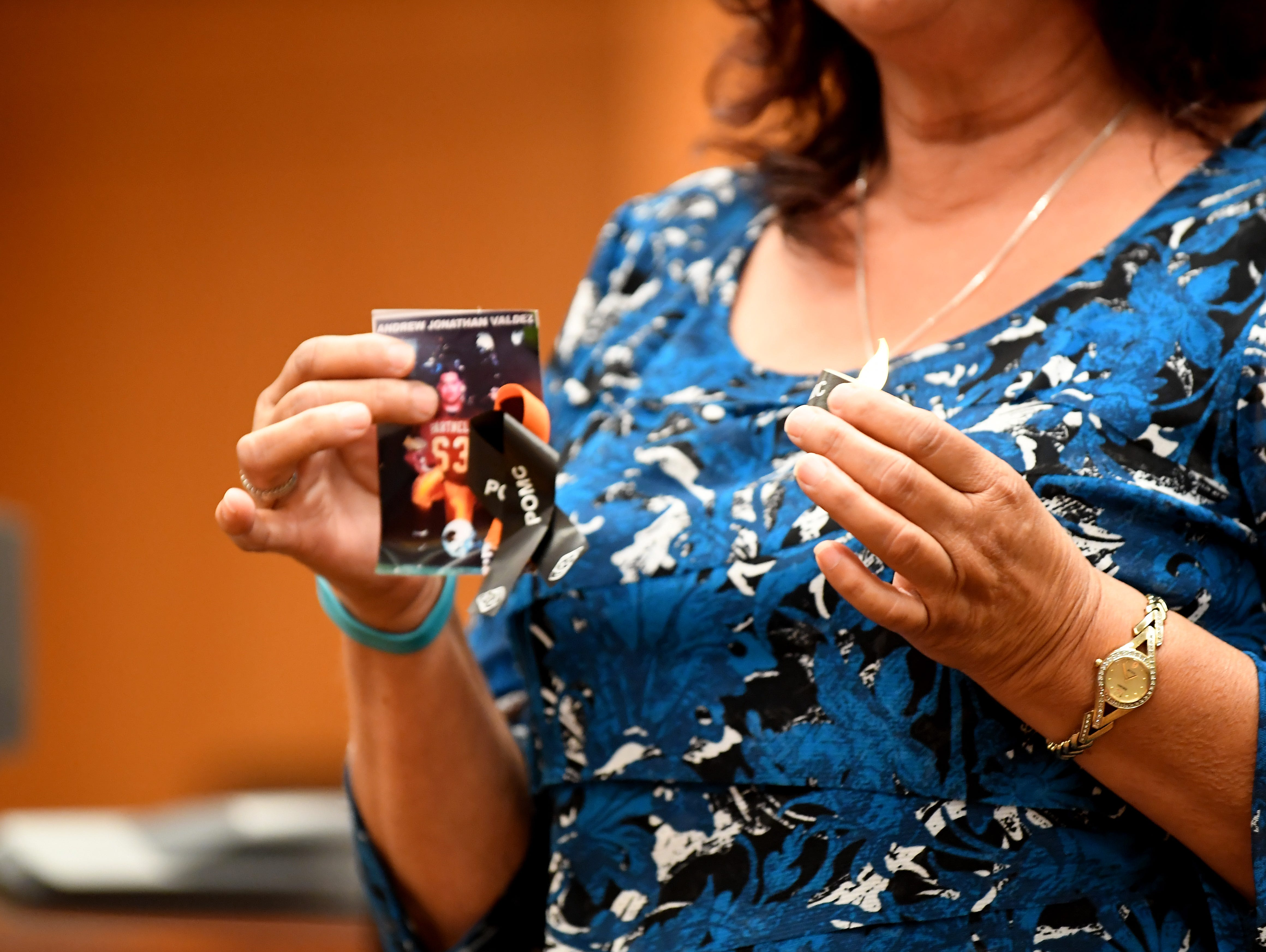 Emily Valdez lights a candle for her son who was killed in 1995 in Castroville.