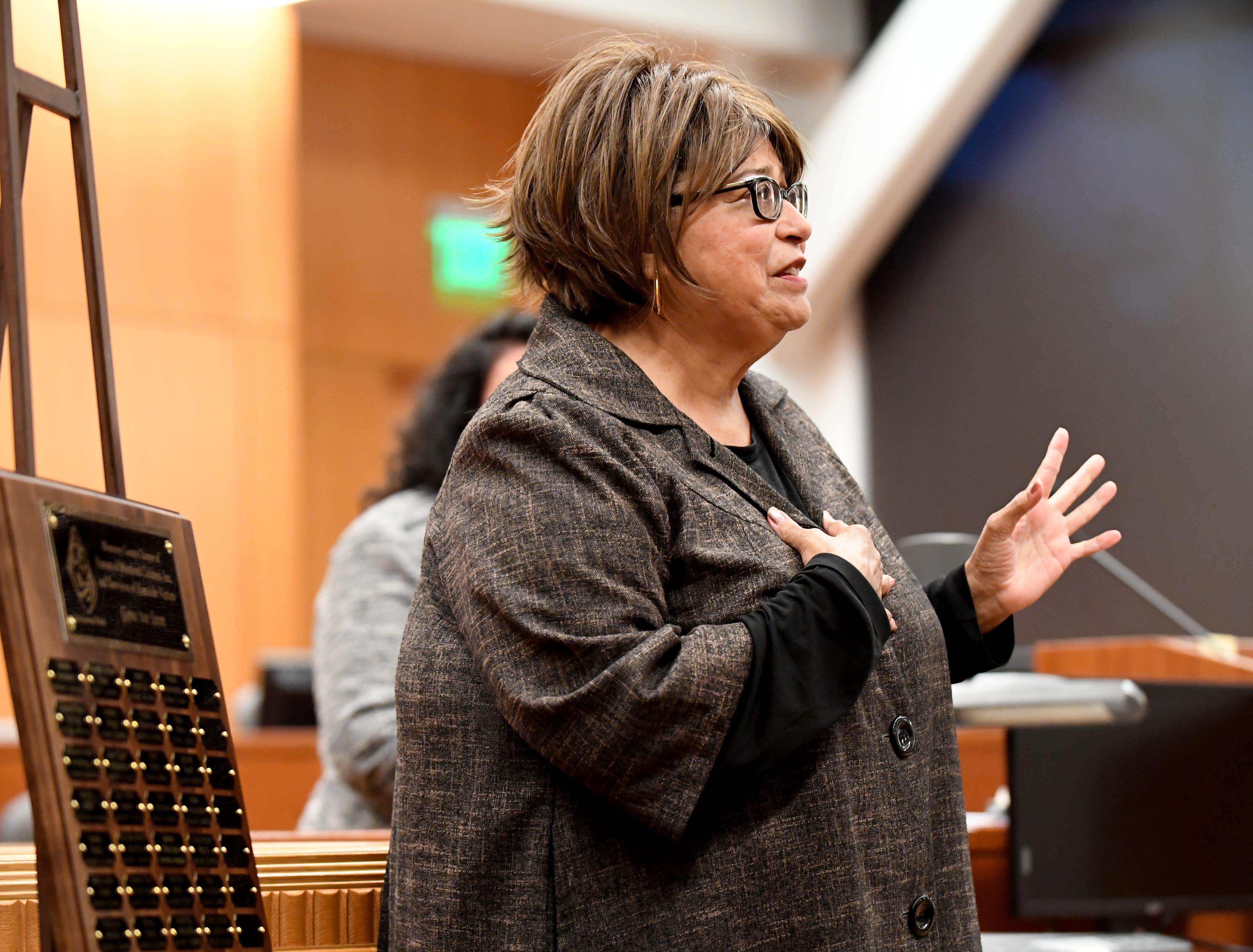 Councilmember Gloria De La Rosa speaks alongside a plaque honoring victims of murder Thursday.