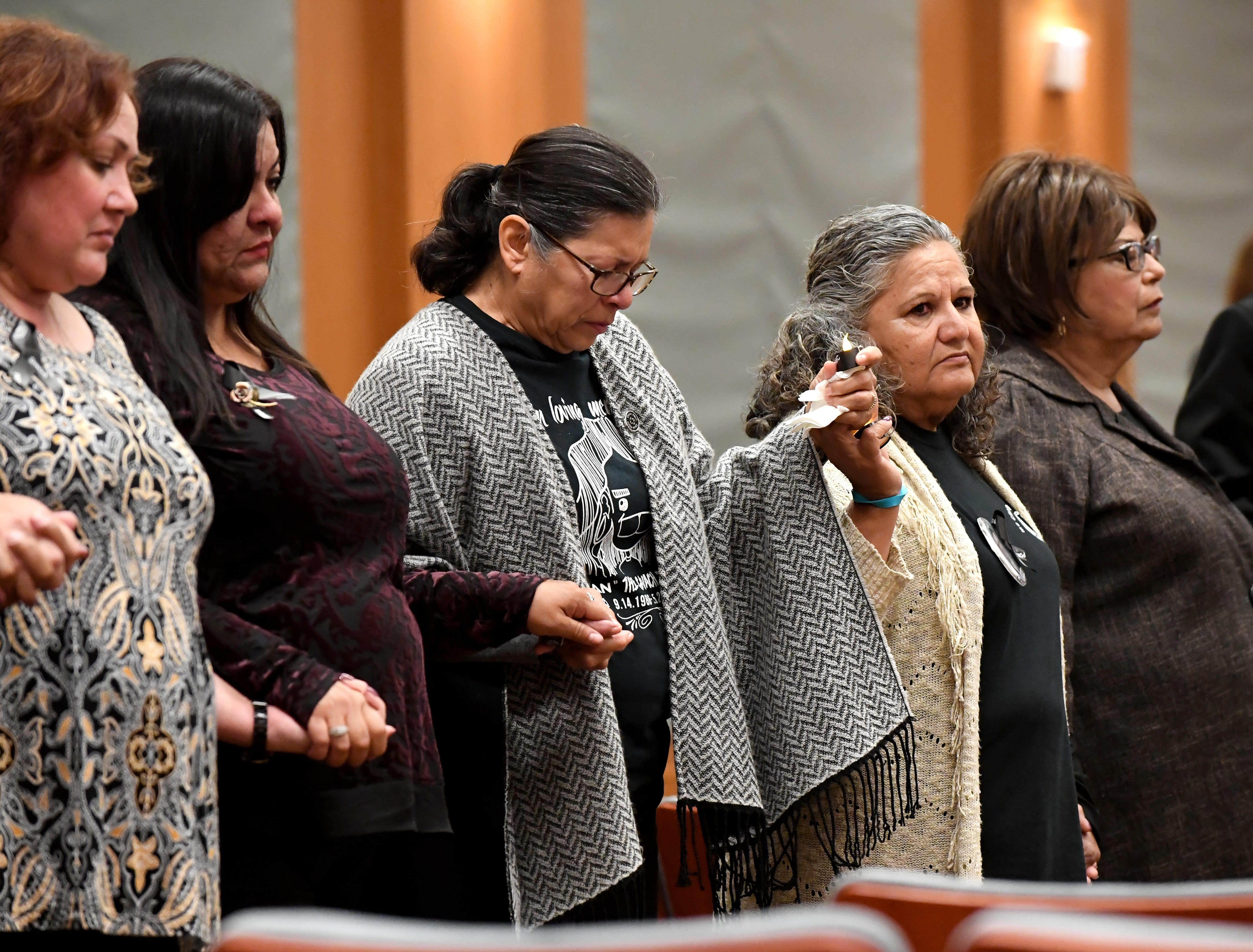 Maria Rodriguez (middle) holds hands with other survivors during the National Day of Remembrance for Murder  Victims ceremony on Thursday. Her son was killed in a hit-and-run at Natividad Road and Los Coches Avenue in 2014.