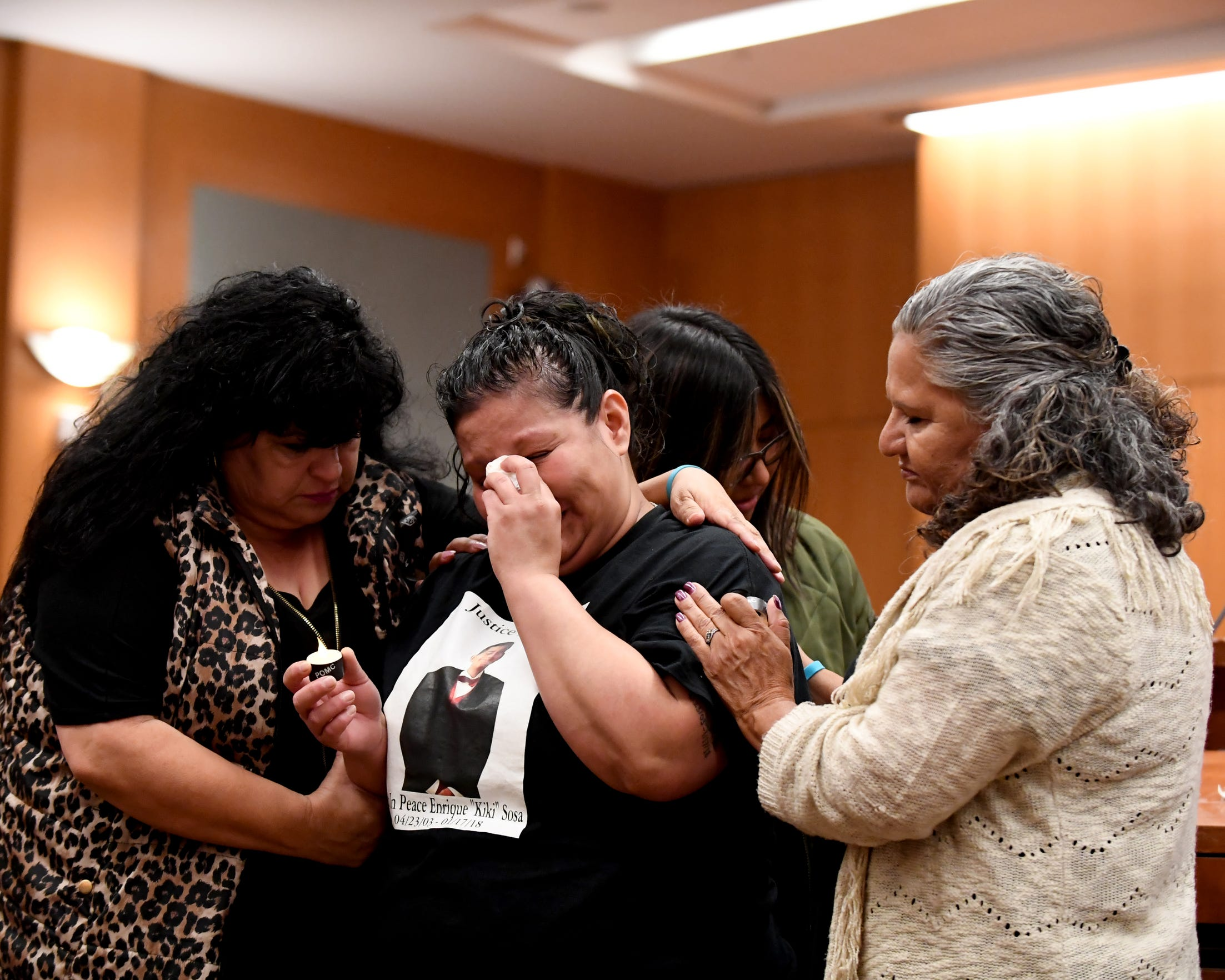 "Debbie Martin (left) and Elsa Sandoval (right) comfort Lenore Sosa and her daughter Cecily Rodriguez. Sosa lost her 14-year-old son Enrique ""Kiki"" Sosa in a shooting on Russell Road in January."