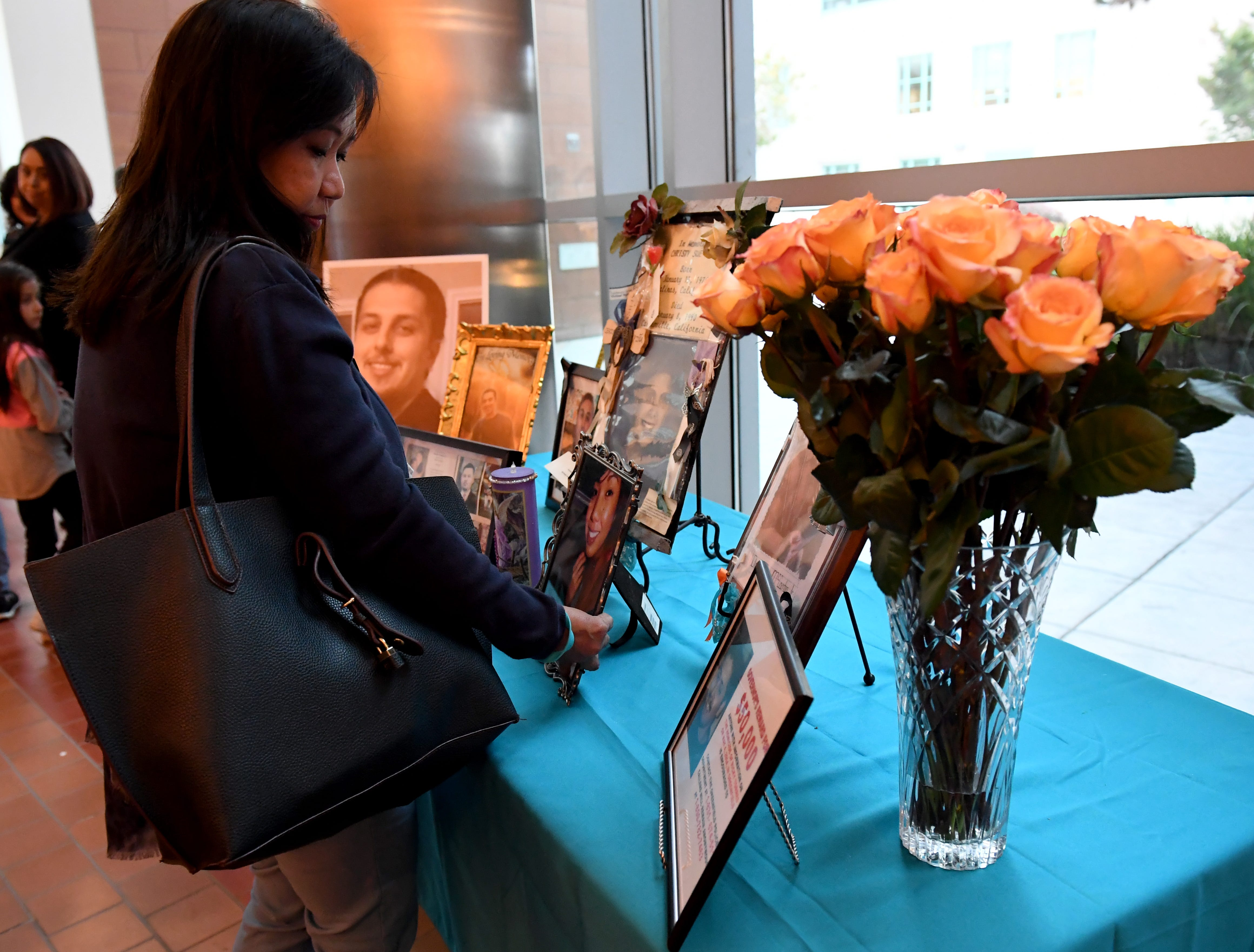 A woman places a photo honoring her loved one on a table at the National Day of Remembrance for Murder Victims ceremony Thursday.