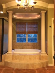 The master bathroom at 1708 Catalina Drive boasts a jet bathtub framed by tall columns.
